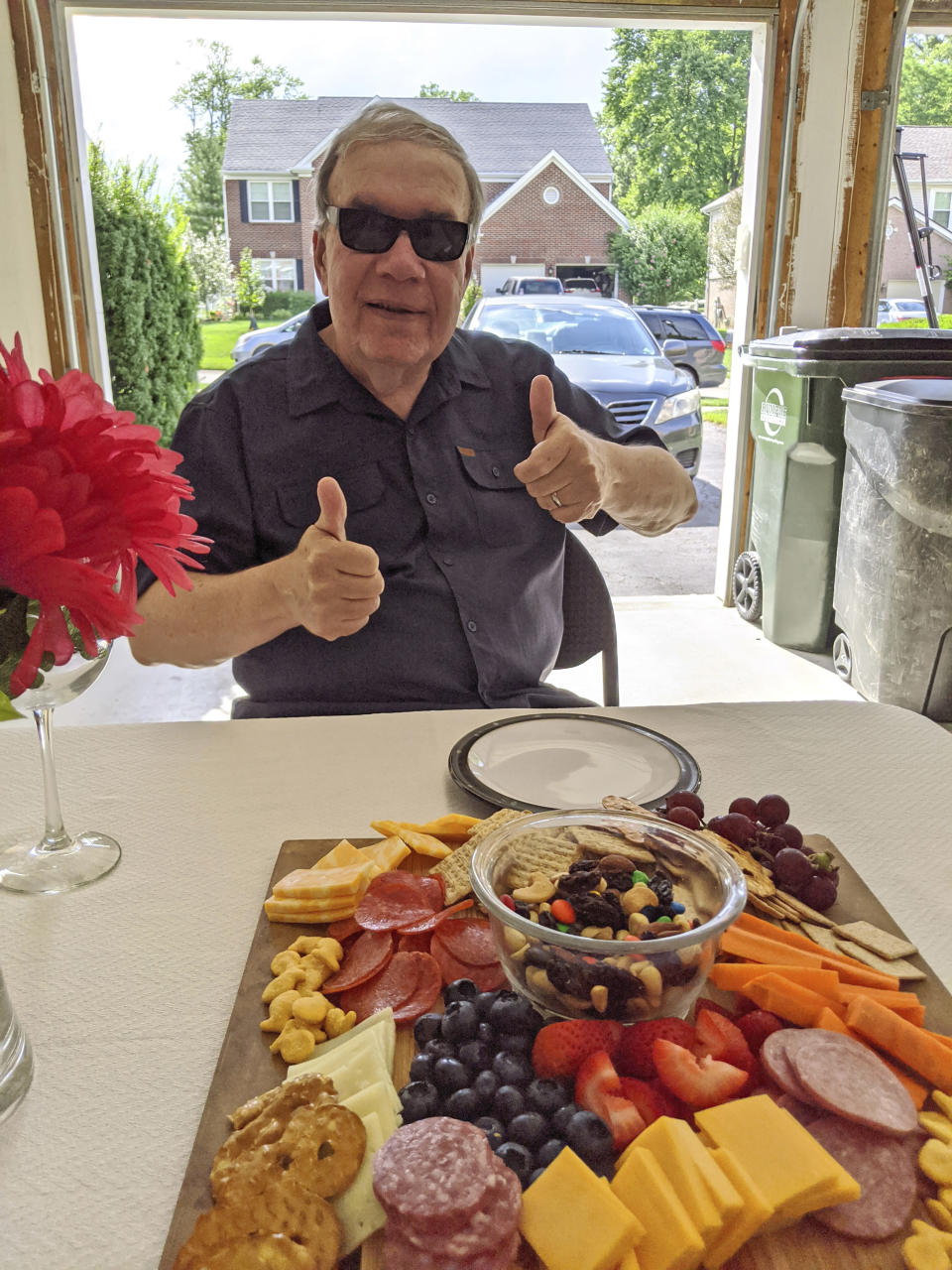 """In this photo provided by courtesy of Nancy Peters, Joe Peters gives a thumbs up before enjoying a charcuterie board at a birthday dinner at one of his children's home, Aug. 1, 2020, in Cincinnati. Joe and Nancy Peters had one of their 11 grandchildren over to visit last week as they began """"cautiously returning to normal,"""" he says. The pandemic and its isolating restrictions have been especially tough for many of the nation's some 70 million grandparents, many at ages when they are considered most vulnerable to the deadly COVID-19 virus. (Nancy Peters via AP)"""