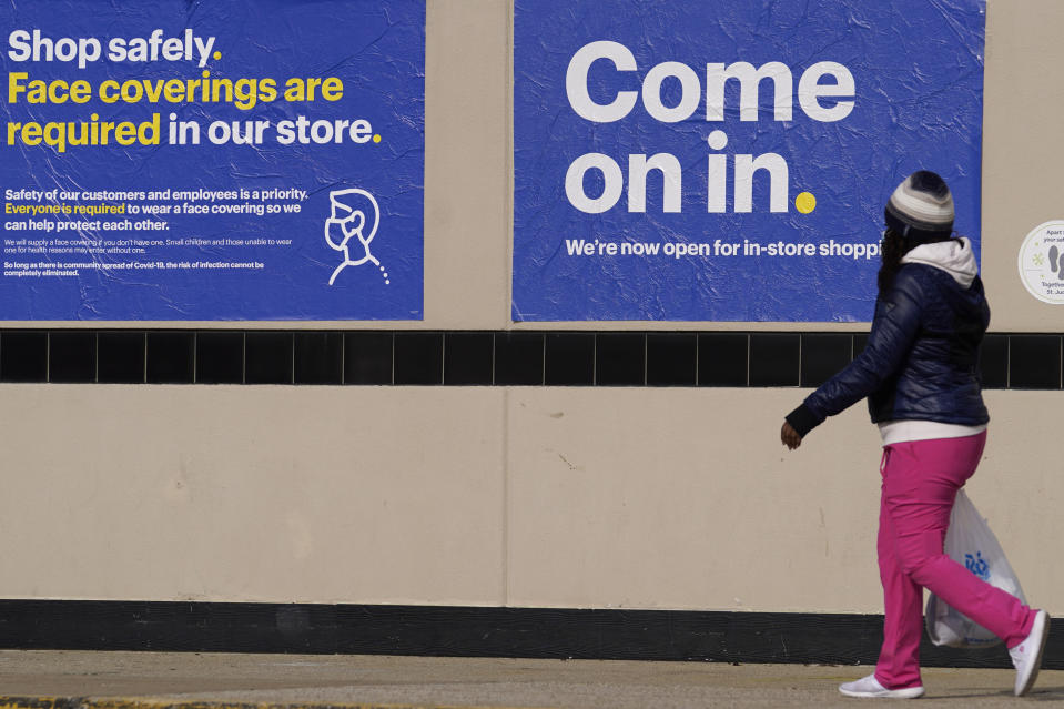 A shopper walks to a retail store as information signs are displayed in Downers Grove, Ill., Sunday, Nov. 29, 2020. (AP Photo/Nam Y. Huh)