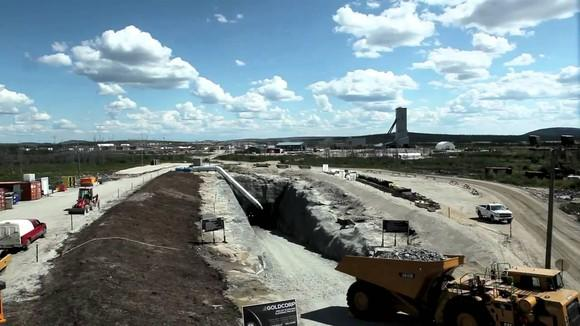 Mining operation with trucks, equipment, and cuts all shown in an arid landscape.