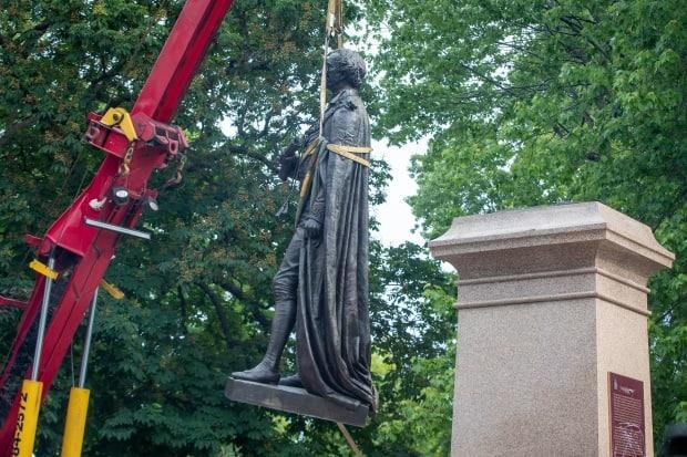 The statue of Sir John A. Macdonald is taken off its pedestal in Kingston, Ont., on Friday.  (Lars Hagberg/The Canadian Press - image credit)