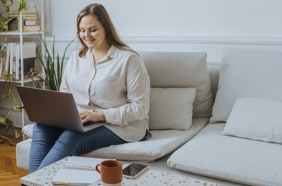 Smiling businesswoman sitting in the living room and working on her laptop computer.