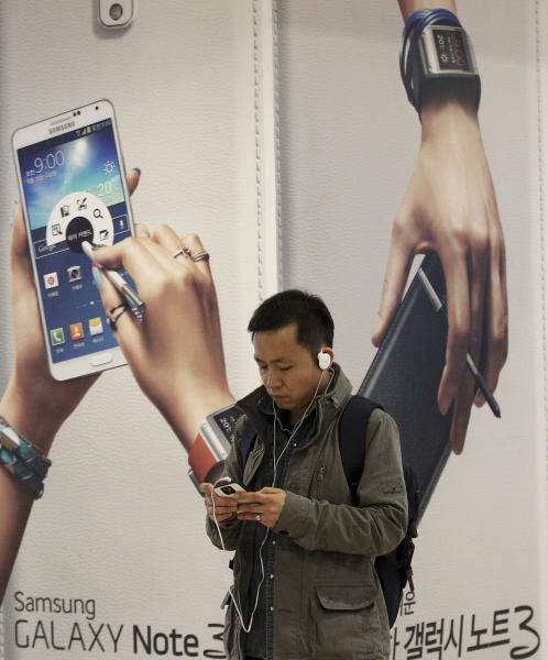 A man uses a smartphone near an advertisement for Samsung Electronics Co.'s Galaxy Note 3 in Seoul, South Korea, Tuesday, April 8, 2014. Declining smartphone prices hit profit at Samsung for a second straight quarter. The consumer technology heavyweight said Tuesday that it expects operating income of about 8.4 trillion won ($8 billion) for the January-March quarter, down 4 percent from a year earlier. (AP Photo/Ahn Young-joon)