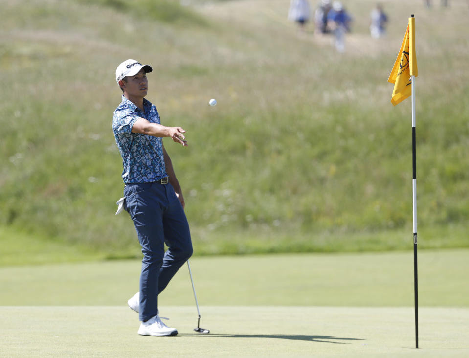 United States' Collin Morikawa gives his ball to his caddie on the 3rd hole during the final round of the British Open Golf Championship at Royal St George's golf course Sandwich, England, Sunday, July 18, 2021. (AP Photo/Peter Morrison)