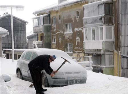 A man smashes ice with a pickaxe next to car covered with ice in Postojna February 3, 2014. REUTERS/Srdjan Zivulovic