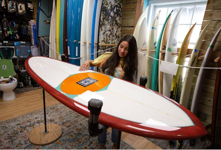 """Assistant store manager Rachael Guzman looks over a """"mini pig"""" surfboard for sale at Lucky Dog Surf Co. in Sea Bright, N.J., on Tuesday. The shop is struggling to keep merchandise stocked at a time when demand for surfing equipment has increased, with many people suddenly seeking solitary outdoor activities during the pandemic."""