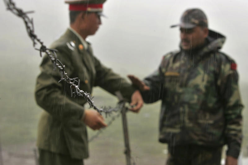 FILE - In this July 5, 2006 file photo, a Chinese soldier, left, and an Indian soldier put into place a barbed wire fence removed temporarily for Chinese officials to cross back to their country after a meeting with their Indian counterparts at the international border at Nathula Pass, in northeastern Indian state of Sikkim. While the recent troop standoff in a remote Himalayan desert spotlights a long-running border dispute between China and India, the two emerging giants are engaged in a rivalry for global influence that spreads much farther afield. (AP Photo/Gurinder Osan, File)