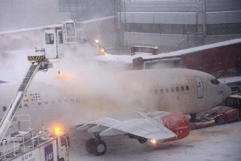 A Boeing 737-600 Scandinavian Airlines, SAS, plane having ice cleared from its fuselage as it stands at terminal 5, Arland airport outside Stockholm, Wednesday Dec. 5, 2012.  Only one runway track is open due to the heavy snow fall and many flights have been canceled. (AP Photo / Johan Nilsson / SCANPIX)  SWEDEN OUT