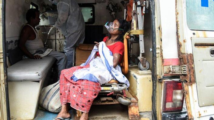An elderly woman with breathing difficulty inhales medication with the help of nebuliser or oxygen mask, inside an ambulance, at MMCH hospital in Guwahati, Assam, India on 25 May 2021.