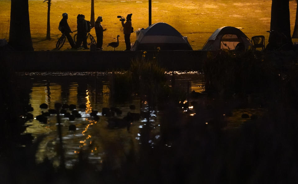 Members of the media interview demonstrators outside their tents in the Echo Park Lake homeless encampment in Los Angeles late Wednesday, March 24, 2021. (AP Photo/Damian Dovarganes)