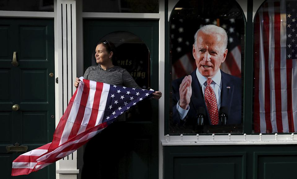A shop owner waves a U.S. flag beside a poster of Joe Biden as the celebration begins in Ballina, Ireland, his ancestral home