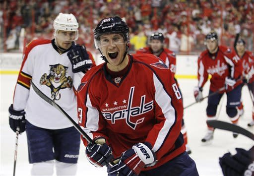 Washington Capitals center Jay Beagle (83) smiles as he skates past Florida Panthers left wing Tomas Fleischmann (14) to celebrate with his bench after scoring a goal during the first period of an NHL hockey game on Thursday, April 5, 2012, in Washington. (AP Photo/Evan Vucci)