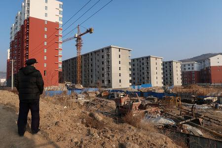 FILE PHOTO - A man looks at a shantytown to be redeveloped, next to apartment buildings, in Fu county in the south of Yanan, Shaanxi province, China January 2, 2019. Picture taken January 2, 2019. REUTERS/Yawen Chen