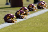 File-This May 14, 2021, file photo shows helmets for the Washington Football Team placed on the sideline during an NFL football rookie minicamp at Inova Sports Performance Center in Ashburn, Va. The NFL has fined the Washington Football Team $10 million and owner Dan Snyder is stepping away from day-to-day operations after an independent investigation into the organization's workplace misconduct. (AP Photo/Susan Walsh, File)