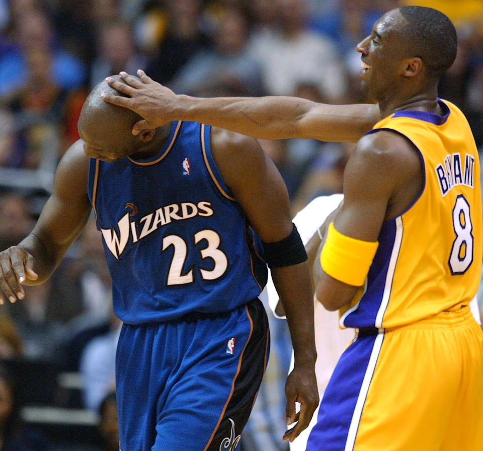 Michael Jordan, left, in a blue Wizards jersey has his head pushed away in jest by Kobe Bryant.