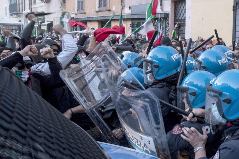 Demonstrators, some waving Italian flags, clash with police in anti-riot gear during a protest against the government's restriction measures to curb the spread of COVID-19, in Rome's Campo dei Fiori Square, Saturday, Oct. 31, 2020. (Roberto Monaldo/LaPresse via AP)