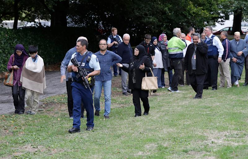 Police escort witnesses away from a mosque in central Christchurch after a mass shooting in New Zealand on March 15, 2019.