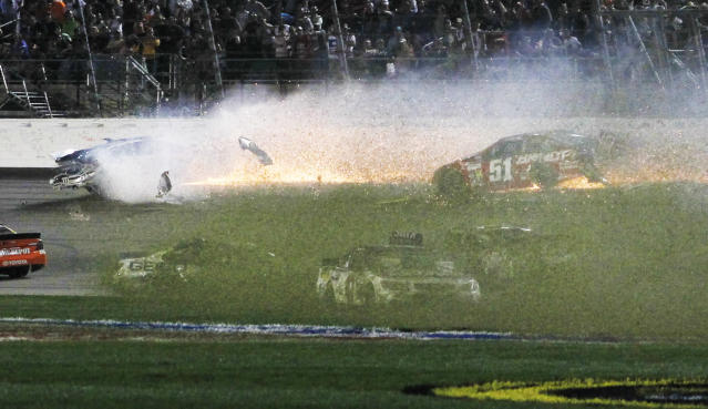 Drivers spin into the infield as David Gilliland, top left, and Justin Allgaier (51) tangle with the wall during a NASCAR Sprint Cup Series auto race at Kansas Speedway in Kansas City, Kan., Saturday, May 10, 2014. (AP Photo/Colin E. Braley)