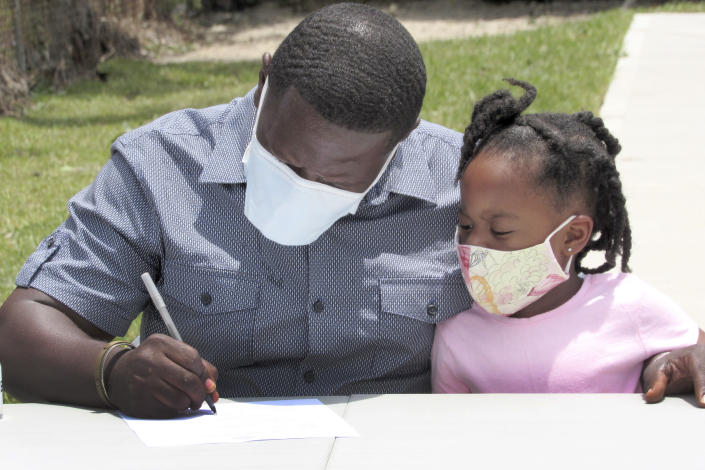 In this photo taken Friday, May 29, 2020, Houston resident Lloyd Nelms sits next to his niece as he signs paperwork before receiving the keys to his new house. Nelms' family home had to be torn down after it was flooded during Hurricane Harvey in 2017. Nelms said he was unable to get help from a city program created to fix homes damaged during Harvey and had to endure hazardous living conditions for more than two years. He turned to the Texas General Land Office to rebuild his home. The city program has finished rebuilding less than 70 homes since beginning in January 2019. (AP Photo/Juan Lozano)