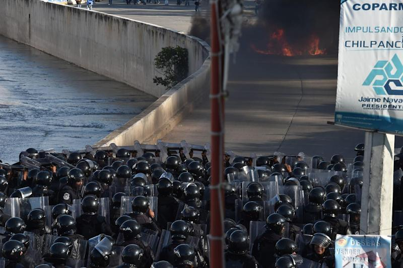 Riot police take positions after students set the Municipal Palace on fire in Chilpancingo, Guerrero, on October 13, 2014 (AFP Photo/Yuri Cortez)