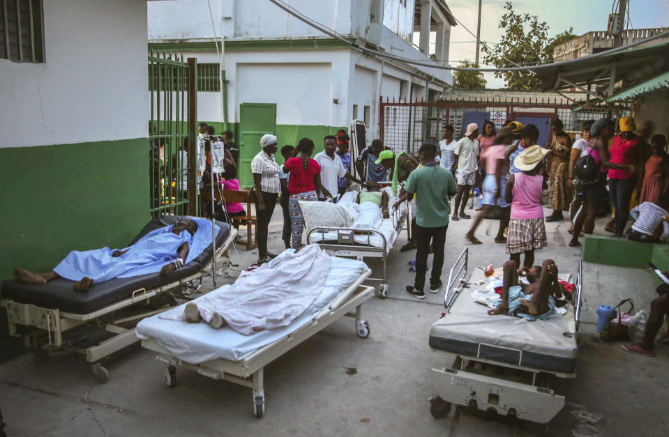 FILE - In this Aug. 15, 2021 file photo, people injured in the Aug. 14th, 7.2 magnitude earthquake, lie on hospital beds in the courtyard of the hospital in Les Cayes, Haiti. (AP Photo/Joseph Odelyn, File)