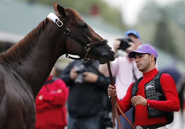 Exercise rider William Delgado holds Kentucky Derby hopeful California Chrome after a morning workout at Churchill Downs Tuesday, April 29, 2014, in Louisville, Ky. (AP Photo/Garry Jones)