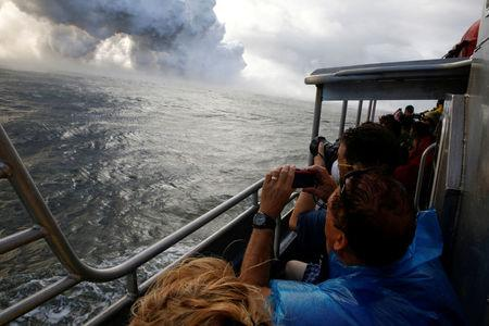 FILE PHOTO: People watch from a tour boat as lava flows into the Pacific Ocean in the Kapoho area, east of Pahoa, during ongoing eruptions of the Kilauea Volcano in Hawaii, U.S., June 4, 2018.  REUTERS/Terray Sylvester/File Photo