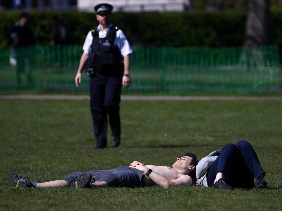 A police officer approaches a sunbather in Greenwich Park, south London. (REUTERS)