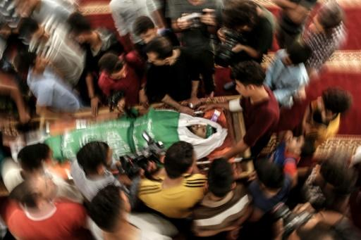 Palestinian mourners in Gaza City pictured on May 15, 2018 surrounding the body of Yazan Tubasi, killed during clashes in Gaza the previous day