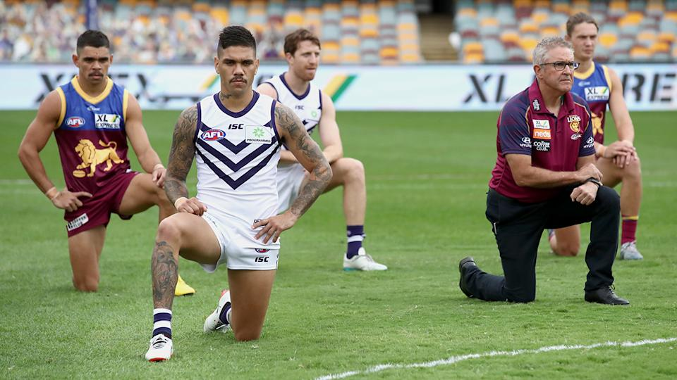 Fremantle and Brisbane players, pictured here taking a knee before their AFL game.