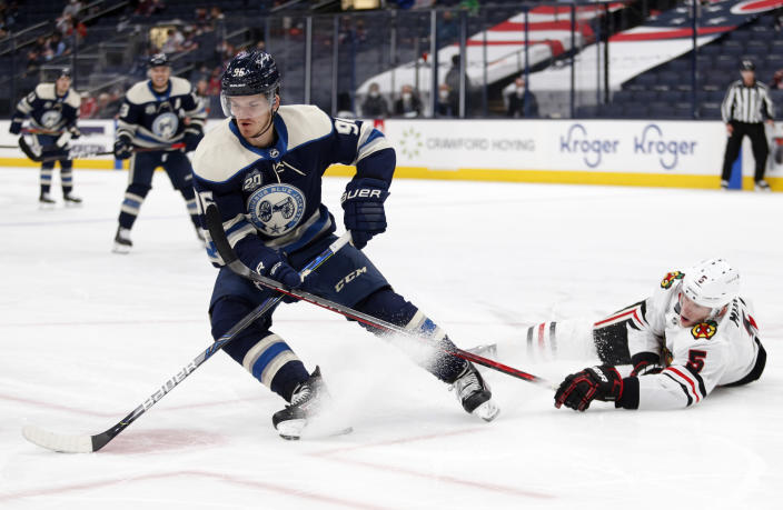 Columbus Blue Jackets forward Jack Roslovic, left, controls the puck against Chicago Blackhawks defenseman Connor Murphy during the second period of an NHL hockey game in Columbus, Ohio, Monday, April 12, 2021. (AP Photo/Paul Vernon)