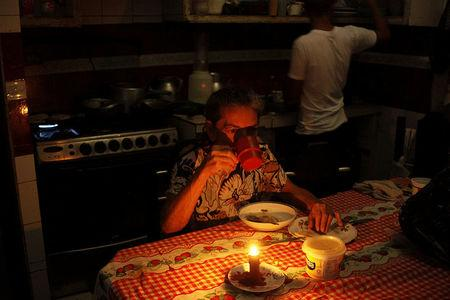 Juana Guerrero uses a candle to illuminate the table while she dines during a blackout in San Cristobal, Venezuela March 13, 2018. Picture taken March 13, 2018. REUTERS/Carlos Eduardo Ramirez