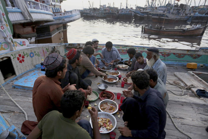 Fishermen break their fast during the Muslim holy fasting month of Ramadan, on a boat in a dockyard, in Karachi, Pakistan, Tuesday, April 20, 2021. (AP Photo/Fareed Khan)