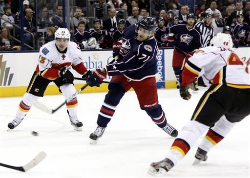 Columbus Blue Jackets' Nick Foligno (71) shoots the puck between Calgary Flames' Mike Cammalleri (13) and Alex Tanguay (40) in the second period of an NHL hockey game in Columbus, Ohio, Friday, March 22, 2013. Foligno scored his second goal of the period on the play. (AP Photo/Paul Vernon)