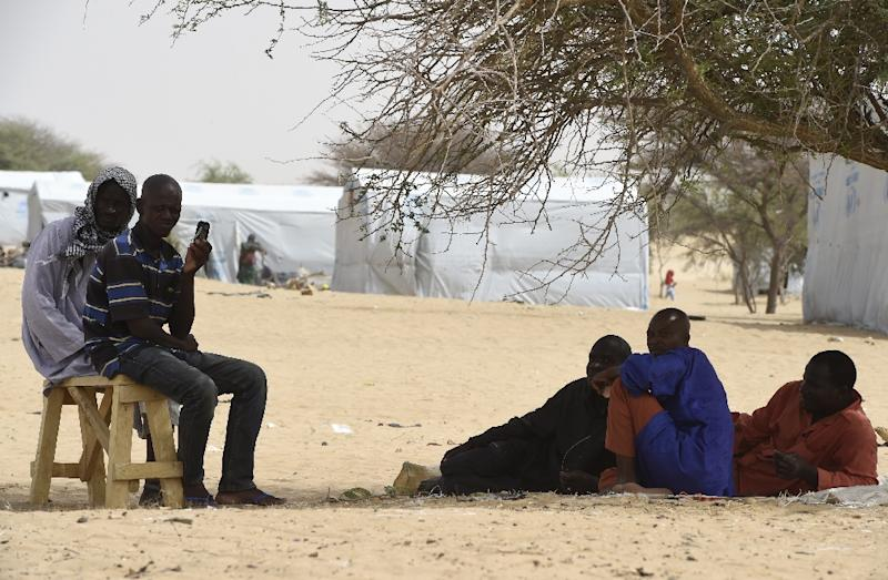 Men sit under trees in the Nigerian refugee camp near Baga Sola in the Lake Chad lake region on April 7, 2015 (AFP Photo/Philippe Desmazes)