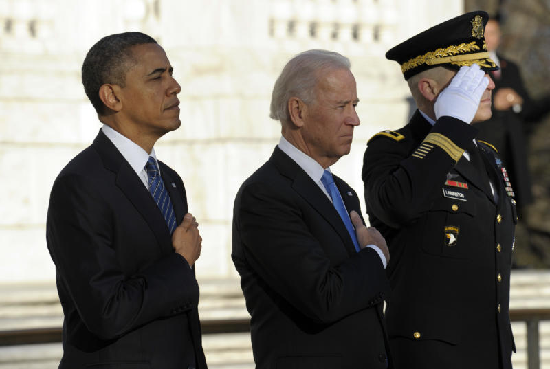President Barack Obama and Vice President Joe Biden, accompanied by Maj. Gen. Michael S. Linnington, Commander of the U.S. Army Military District of Washington, listen to Taps after placing a wreath at the Tomb of the Unknowns at Arlington National Cemetery in Arlington, Va., Sunday, Jan. 20, 2013.  (AP Photo/Susan Walsh)