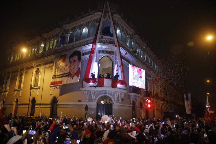 Pedro Castillo celebrates with his running mate Dina Boluarte after being declared president-elect of Peru by election authorities, from the balcony of his campaign headquarters in Lima Peru, Monday, July 19, 2021. Castillo was declared president-elect more than a month after the elections took place and after opponent Keiko Fujimori claimed that the election was tainted by fraud. (AP Photo/Guadalupe Prado)