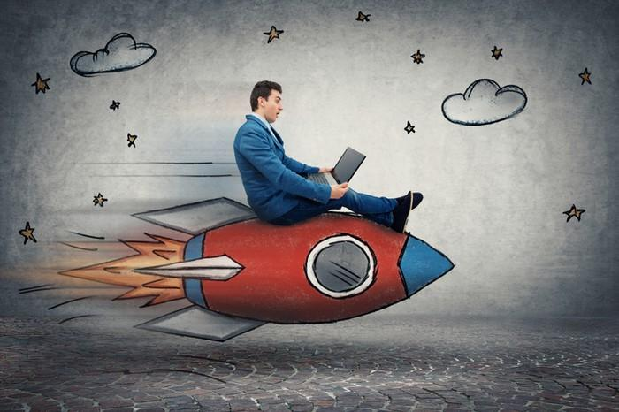A businessman checking his laptop while riding a cartoon rocket.