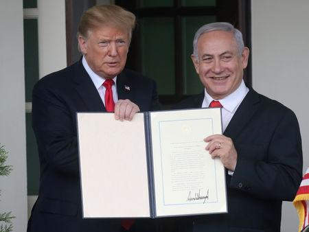 FILE PHOTO: U.S. President Donald Trump and Israel's Prime Minister Benjamin Netanyahu hold up a proclamation recognizing Israel's sovereignty over the Golan Heights as Netanyahu exits the White House from the West Wing in Washington, U.S. March 25, 2019. REUTERS/Leah Millis/File Photo