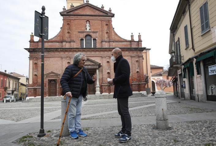 In this photo taken on Thursday, March 12, 2020, Codogno's mayor Francesco Passerini, right, talks to a citizen in Codogno, Italy. The northern Italian town that recorded Italy's first coronavirus infection has offered a virtuous example to fellow Italians, now facing an unprecedented nationwide lockdown, that by staying home, trends can reverse. Infections of the new virus have not stopped in Codogno, which still has registered the most of any of the 10 Lombardy towns Italy's original red zone, but they have slowed. For most people, the new coronavirus causes only mild or moderate symptoms. For some it can cause more severe illness. (AP Photo/Antonio Calanni)