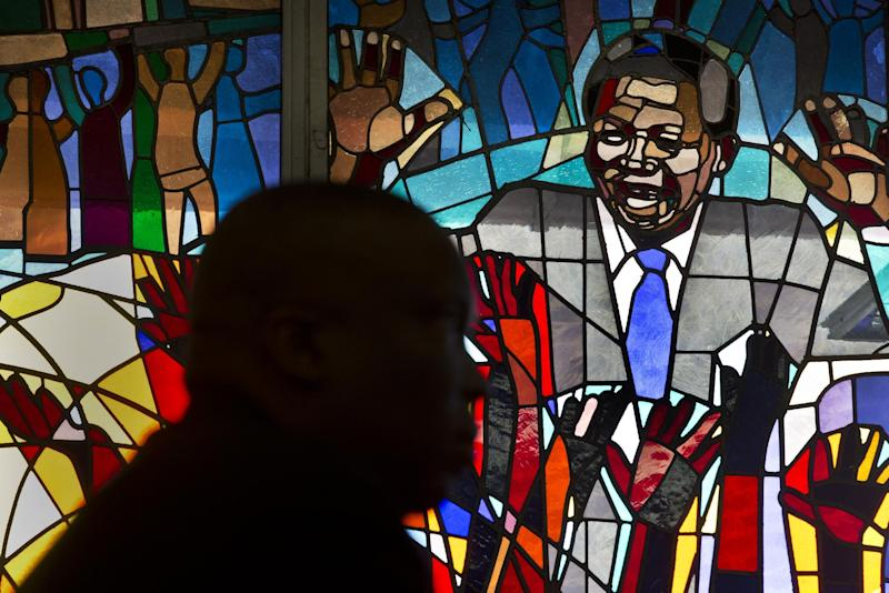 A mourner is silhouetted in front of a stained-glass window of Nelson Mandela at a morning mass in his memory at the Regina Mundi church, which became one of the focal points of the anti-apartheid struggle, in Soweto, Johannesburg, South Africa Sunday, Dec. 8, 2013. South Africans flocked to houses of worship Sunday for a national day of prayer and reflection to honor Nelson Mandela, starting planned events that will culminate in what is expected to be one of the biggest funerals in modern times. (AP Photo/Ben Curtis)