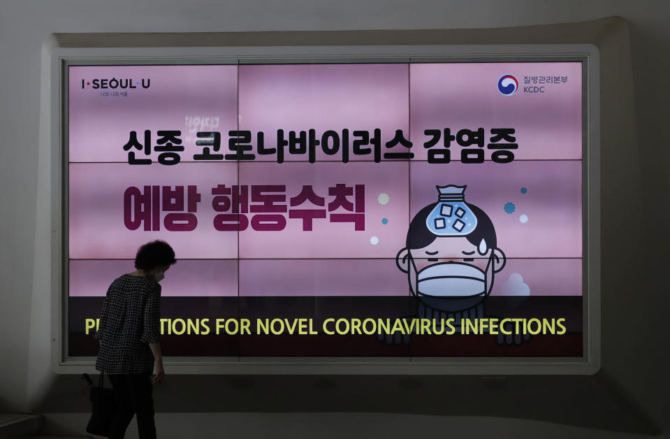 A woman wearing a face mask walks near a screen displaying precautions against the coronavirus in Seoul, South Korea, Friday, Aug. 14, 2020. South Korea reported over 100 new virus cases Friday, one of its biggest daily jumps in months, as officials express concerned that infections are getting out of control in cities as people increasingly venture out in public. (AP Photo/Lee Jin-man)