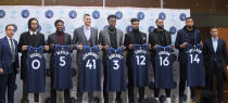 Minnesota Timberwolves President of NBA Basketball Operations Gersson Rosas, left, and head coach Ryan Saunders, right, pose with new players during an NBA basketball news conference where they were introduced to the media, Friday, Feb. 7, 2020, in Minneapolis. The players, from second left, are: D'Angelo Russell, Malik Beasley, Juan Hernangomez, Jarred Vanderbilt, Jacob Evans III, James Johnson and Omari Spellman. (AP Photo/Jim Mone)