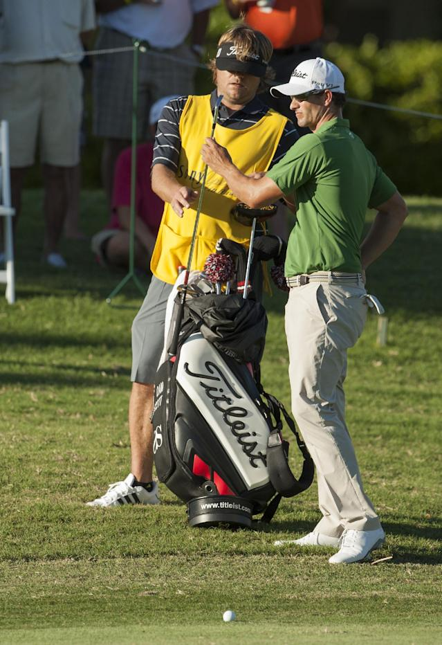 Caddie Benji Weatherly, left, hands club to Adam Scott on the 18th fairway during the second round of the Sony Open golf tournament, Friday, Jan. 10, 2014, in Honolulu. (AP Photo/Marco Garcia)