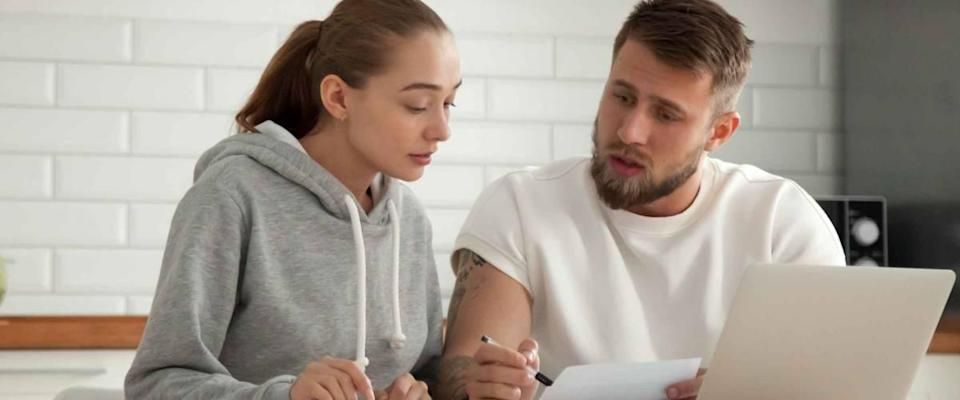 Focused young couple in kitchen discussing whether to refinance their mortgage.