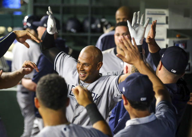 New York Yankees Aaron Hicks (31) gets high fives in the dugout after a two run home run against the Texas Rangers in the ninth inning of a baseball game Monday, May 21, 2018, in Arlington, Texas. (AP Photo/Richard W. Rodriguez)