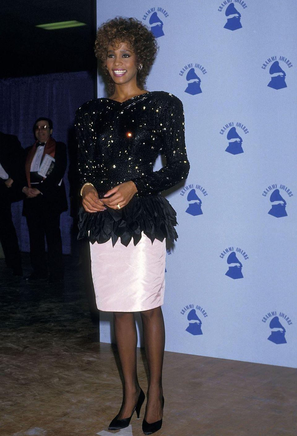 <p>Whitney Houston attends the 29th annual Grammy Awards in a shimmery peplum top and white pencil skirt. </p>