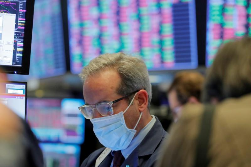 FILE PHOTO: A trader wears a mask as he works on the floor of the New York Stock Exchange (NYSE) as the building prepares to close indefinitely due to the coronavirus disease (COVID-19) outbreak in New York