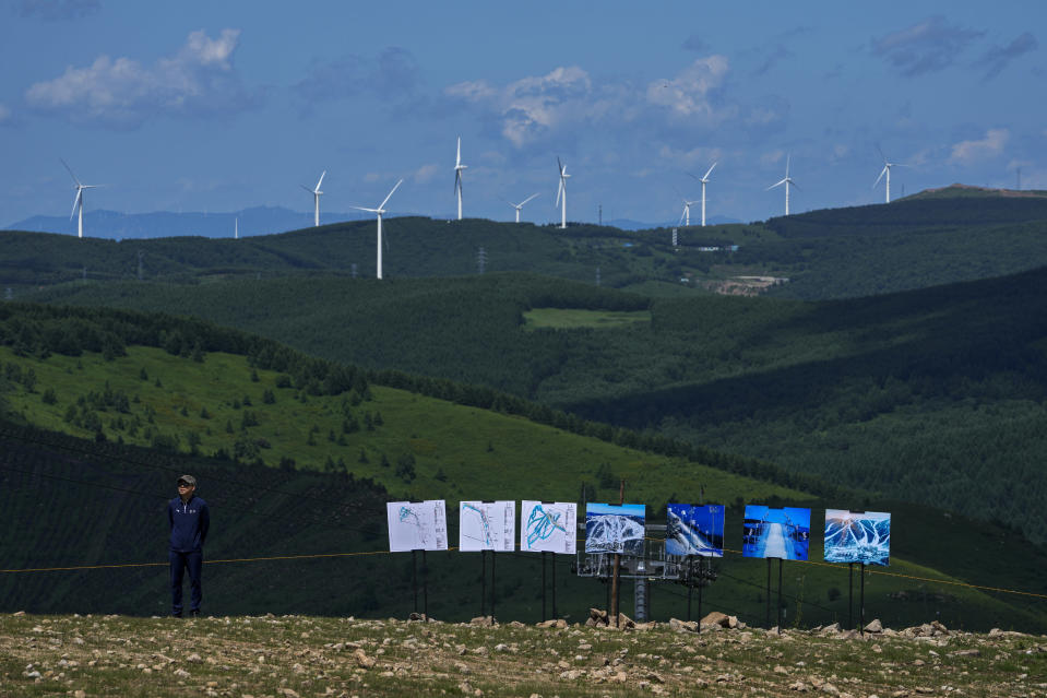 A Chinese officer stands near the pictures showing the snowed venues for Beijing 2022 Olympic and Paralympic Winter Games and Paralympic Winter Games, at Genting Snow Park, during a media tour in Zhangjiakou in northwestern China's Hebei province on Wednesday, July 14, 2021. (AP Photo/Andy Wong)