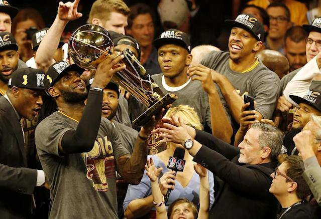 Cleveland Cavaliers forward LeBron James hoists the Larry O'Brien trophy after winning the NBA Finals. (AFP Photo/Beck Diefenbach)