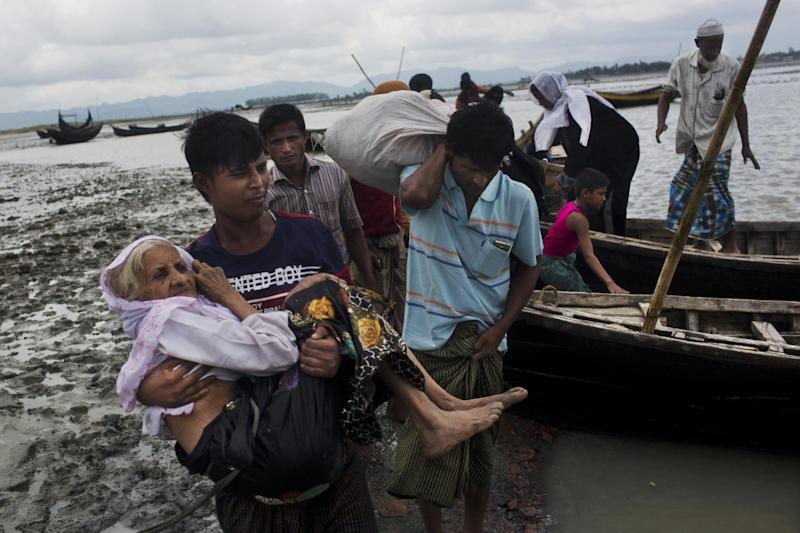 Refugee: A Rohingya ethnic minority from Myanmar carries an elderly woman: AP